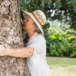 Retired woman hugging a tree — Stock Photo #29454869