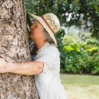 Retired woman hugging a tree — Stock Photo