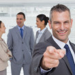 Cheerful businesman pointing at camera with colleagues on backgr — Stock Photo #29454939