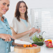 Woman cutting carrots with her friend mixing salad — Stock Photo
