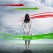 Businesswoman looking at red and green arrows — Stock Photo
