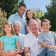 Cheerful multi generation family sitting on a bench in park — Foto Stock