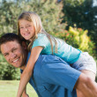 Daughter getting piggy back from dad — Stock Photo