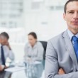 Serious businessman posing with coworkers on background — Stock Photo