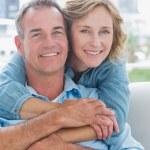 mujer feliz abrazando a su marido en el sofá por detrás — Foto de Stock