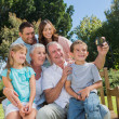 Family sitting on a bench taking photo of themselves — Foto de Stock