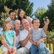 Family sitting on a bench taking photo of themselves — Stockfoto
