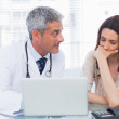 Serious docter showing something on laptop to his patient — Stock Photo