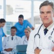 Experienced doctor posing with colleagues in background — Stock Photo