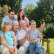 Multi generation family sitting on a bench taking photo of thems — Stock fotografie