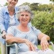 Smiling woman in wheelchair with her daughter — Stock Photo #29455783