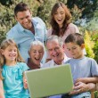 Happy multi generation family with a laptop sitting in park — Stock Photo #29456173