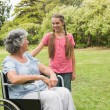 Granddaughter with grandmother in her wheelchair — Stock Photo
