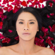Attractive dark haired model lying in rose petals — Stock Photo