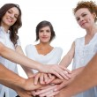 Stock Photo: Cheerful models joining hands in circle and looking at camera