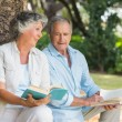 Older couple reading books together sitting on tree trunk — Stock Photo