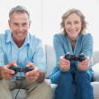 Happy couple playing video games together on the couch — Stock Photo