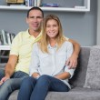 Happy young couple sitting on their couch — Stock Photo