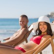 Young couple on their deck chairs smiling at camera — Stock Photo #29456555
