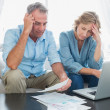 Stock Photo: Worried couple paying their bills online with laptop