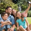 Smiling family in a park taking photos — Stok fotoğraf