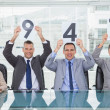 Stock Photo: Cheerful interview panel holding signs giving marks