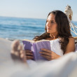 Woman lying on hammock holding book and thinking — Stock Photo