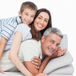 Smiling little boy lying on his parents on sofa — Stock Photo #29457721