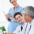 Happy nurse listening to doctors talking about something on thei — Stock Photo #29457741