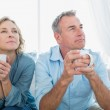 Thoughtful middle aged couple sitting on the couch having coffee — Stock Photo