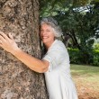 Smiling older woman hugging a tree — Stock Photo