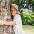 Retired woman hugging a tree smiling at camera — Stock Photo