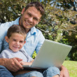 Smiling son and dad with a laptop — Stock Photo