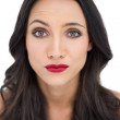 Doubtful dark haired woman with red lips — Stock Photo