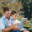 Dad and son playing with a tablet pc in a park — Stock Photo