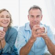 Content middle aged couple sitting on the couch having coffee — Stock Photo