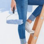 Woman holding paint roller climbing ladder — Stock Photo