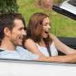 Laughing couple driving in a silver convertible — Stock Photo