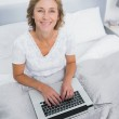 Smiling blonde woman in bed using her laptop — Stock Photo