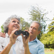 Woman holding binoculars with partner — Stockfoto
