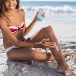 Smiling woman applying sun cream on her leg — Stock Photo