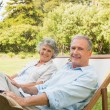 Stock Photo: Happy mature couple sitting on sun loungers