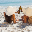 Attractive blonde and brunette in bikinis clinking glass bottles — Stock Photo