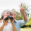 Man showing something to his wife holding binoculars — Stock Photo