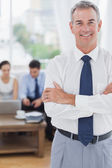 Executive standing on foreground with colleagues on background — Stock Photo