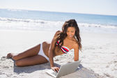 Sexy young woman in bikini using her laptop — Stock Photo