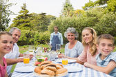 Happy extended family waiting for barbecue being cooked by father — Stock Photo