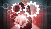 Businessman selecting futuristic cog and wheel interface — Stock Photo