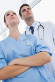 Serious doctor and surgeon looking away — Stock Photo