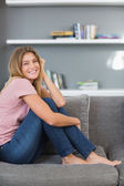 Pretty blonde sitting on her sofa — Stock Photo